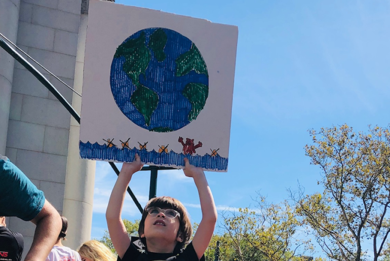 boy holding sign with drawing of earth