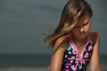 Sad tween girl at the beach.