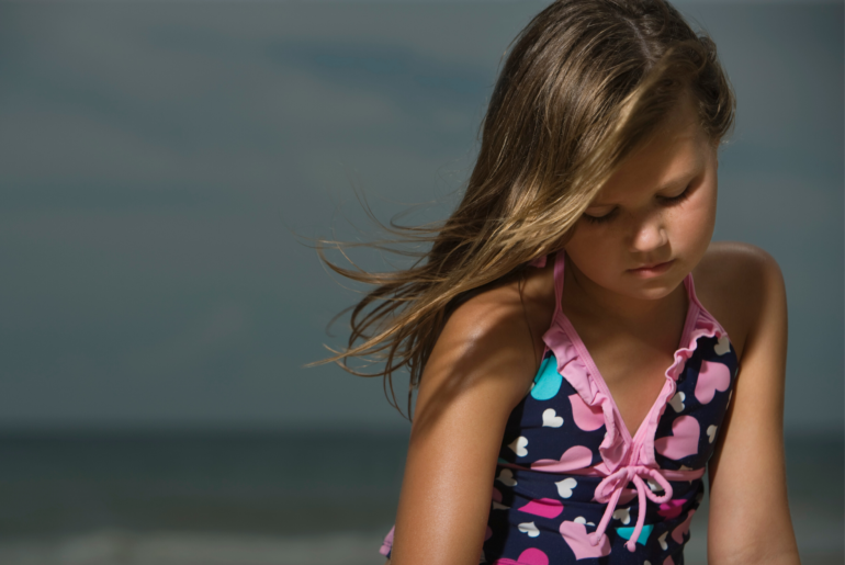 Sad tween girl at the beach.