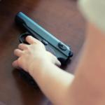 Child's hand reaching for a hand gun.