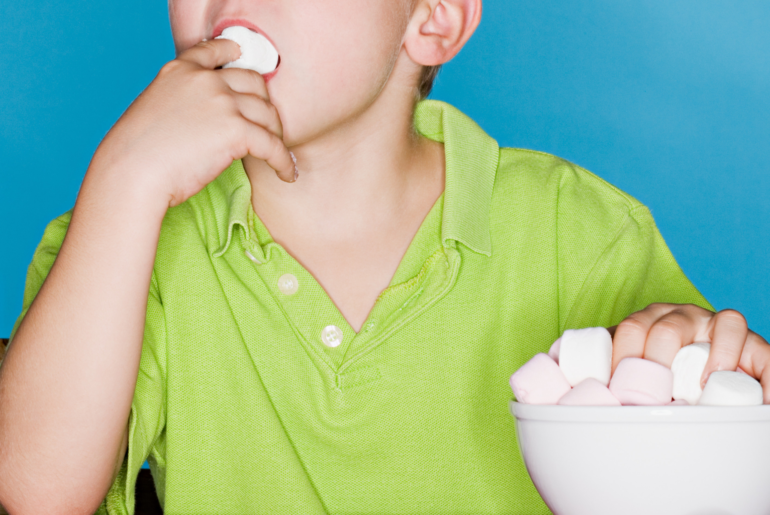 Boy eating a marshmallow while reaching for another in a bowl full of marshmallows.