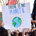 """A hand drawn protest poster is held up by a marcher. It reads """"There is no planet b."""""""