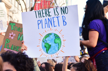 "A hand drawn protest poster is held up by a marcher. It reads ""There is no planet b."""