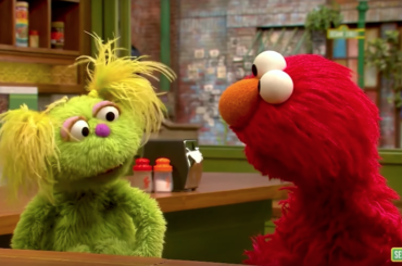 Karli, the muppet, speaking with Elmo.