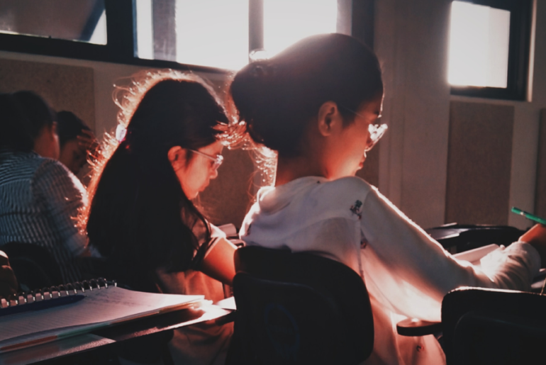 Students sitting in their desks in a classroom while the afternoon sun shines through a window.