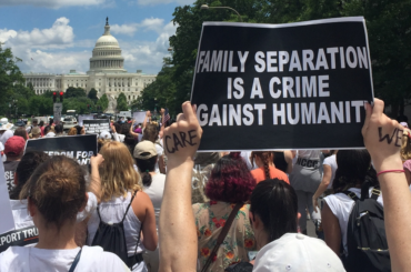 "Marcher holds up a sign that reads ""family separation is a crime against humanity"" in front of the white house."