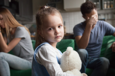 A man and a woman are in conflict while their daughter is between them looking directly at the camera.