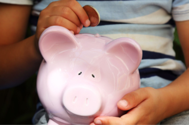 Photo of a child putting a coin into a piggy bank.