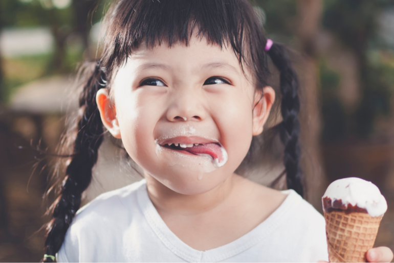 Asian girl with braids licks her bottom lip of ice cream while holding an ice cream cone.