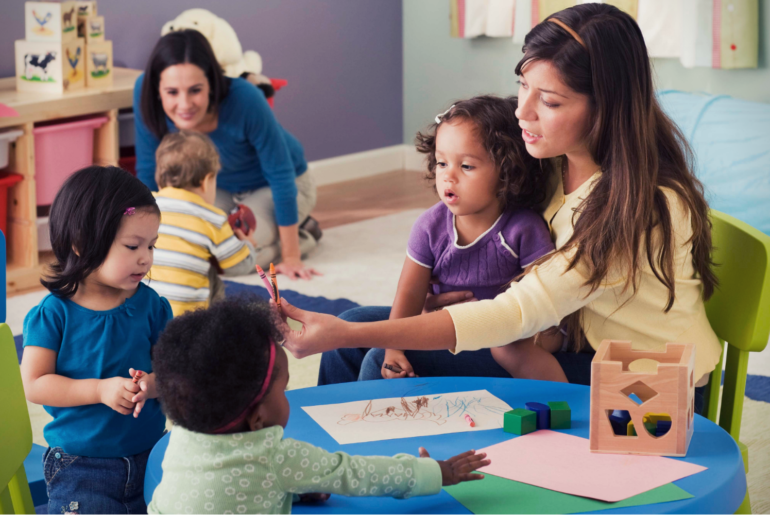 Two teachers teaching three toddlers in a classroom.