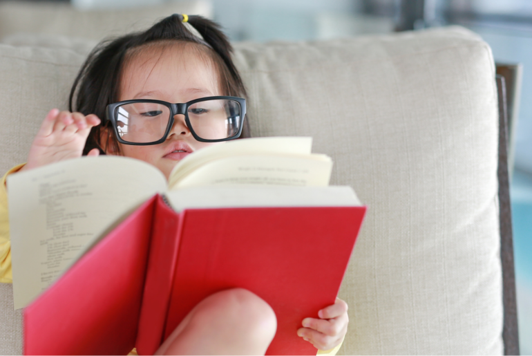 Toddler reading a big red book with a parent's glasses.