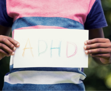"""Midsection photo of a child holding a crayon drawing that reads """"ADHD."""""""