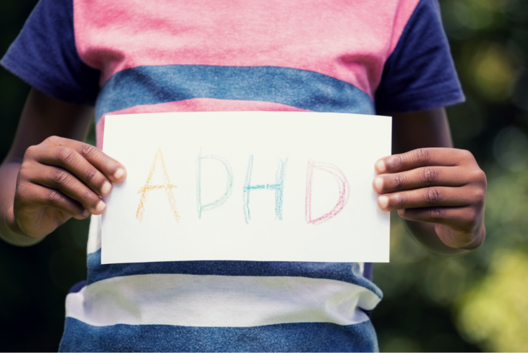 "Midsection photo of a child holding a crayon drawing that reads ""ADHD."""