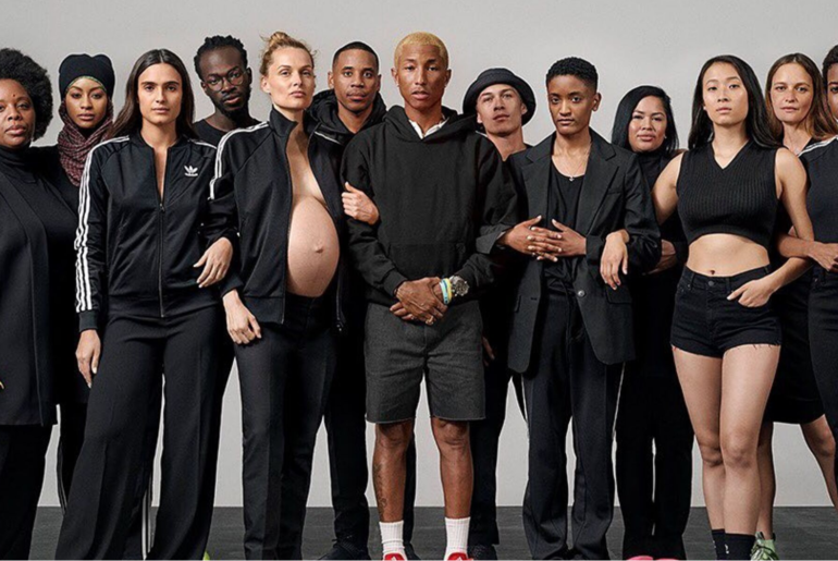 Photo of Pharrell Williams standing surrounded my a diverse group of women.