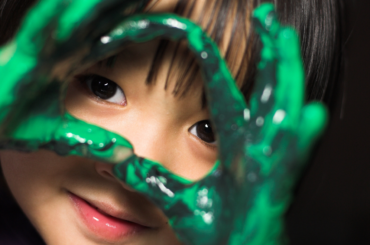 A child with green finger paint on their hands looking at the camera.