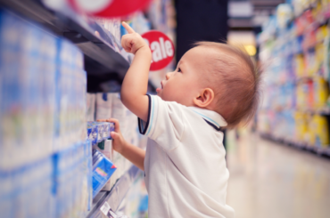 A toddler in a super market aisle points at a package.