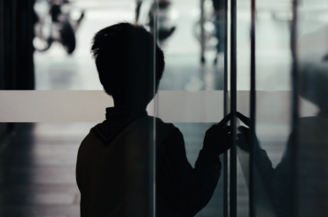 Silhouette of a child stepping through a glass door.
