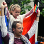 Man holding a gay pride flag carries his daughter on his shoulders.