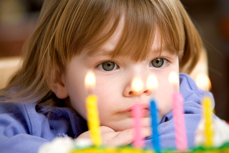 Child looking at the candles on their birthday cake.