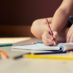 Child doodling in a notebook with a colored pencil.