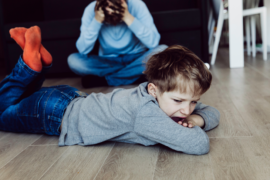 Angry child in the foreground with stressed parent in the background.