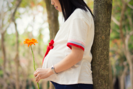 Pregnant woman holding a flower.