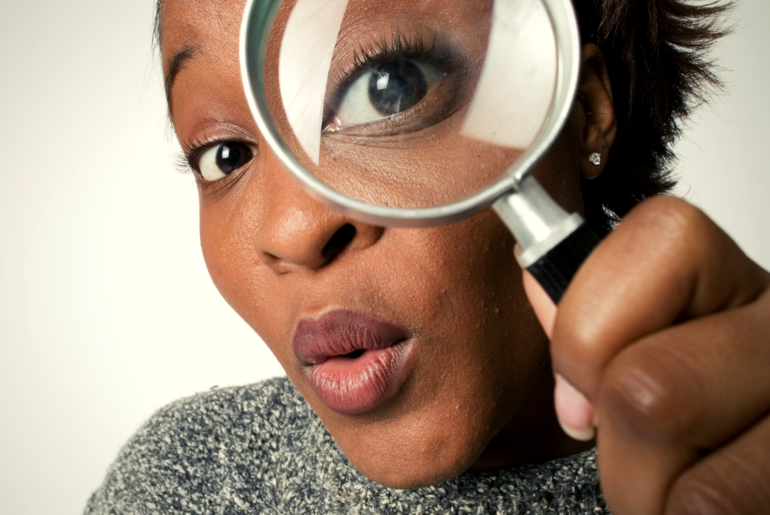 Woman looking through a magnifying glass at the camera.