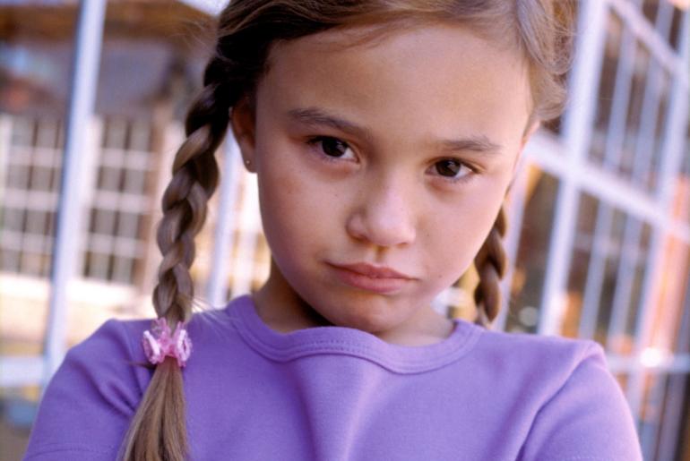 Rebellious looking girl standing outside of school.