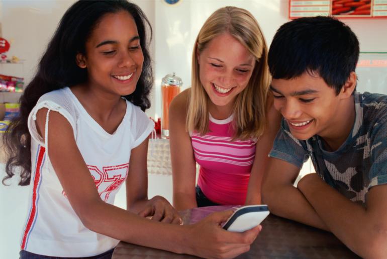 Teens share a digital device.
