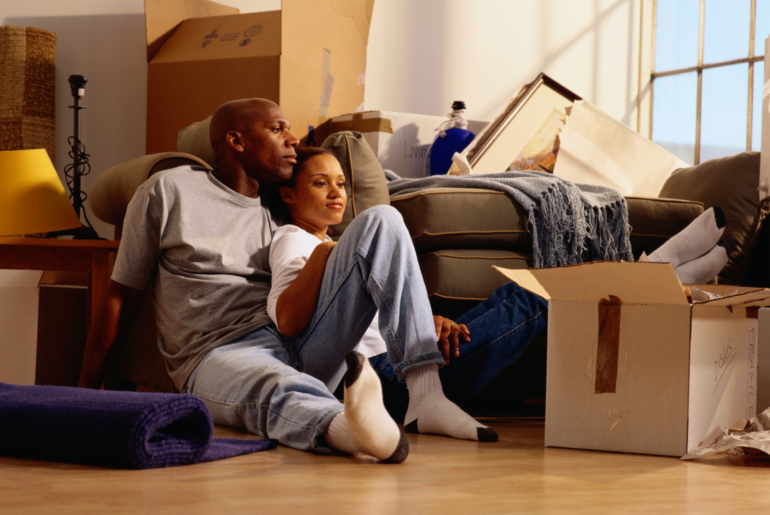 Couple resting while unpacking their belongings.