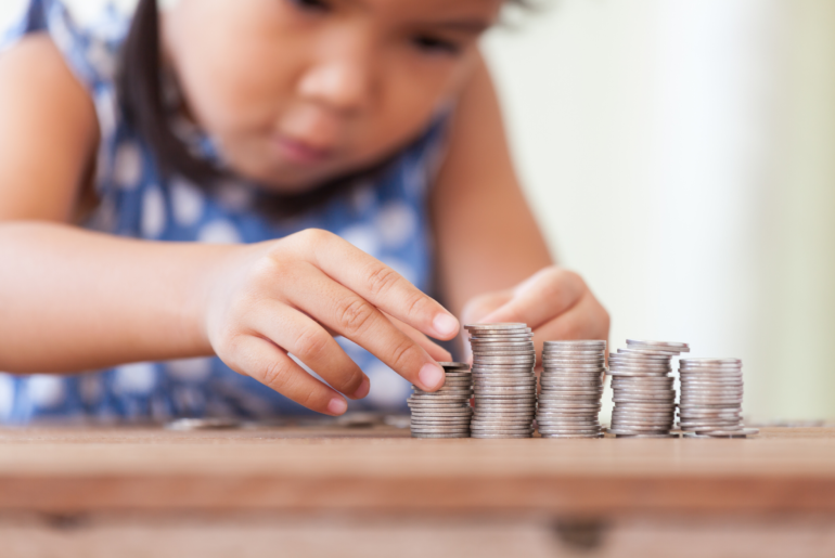 Girl stacks coins in columns.