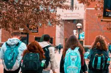 HIgh school students wearing backpackswalking toward the entrance of their highschool.