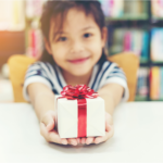 Girl holding a small wrapped gift.