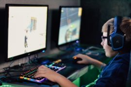 Boy with a headset and his hands on a keyboard looking at a game screen.