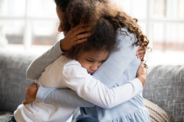 Mother hugging her daughter.