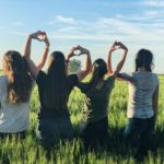 Girls standing in a field weaver their arms and hands together to form hearts.