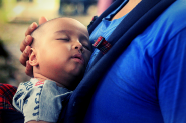 Baby sleeping in a carrier strapped to his father's chest.