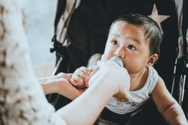 Baby getting fed milk in a bottle.