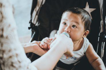 Baby getting fed milk in a bottle.