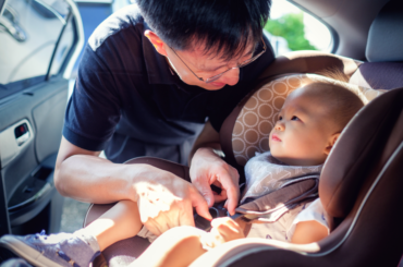 Dad putting his baby into the car seat.