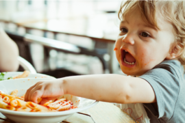 Boy eating from a bowl of pasta and sauce.