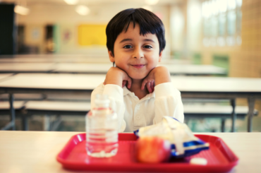 Boy sitting at school lunch table.