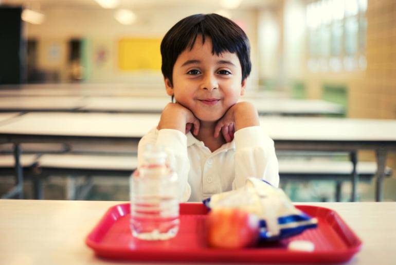 Boy sitting at school lunch table.