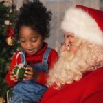 Girl on Santa's lap looking at an ornament.