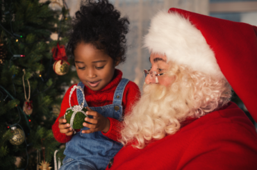 Girl on Santa's lap looking at an ornament.