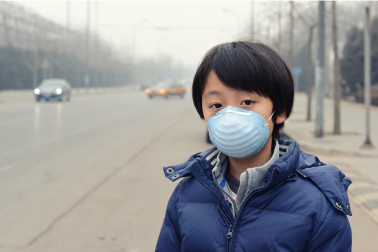 Child breathing through a surgical mask.