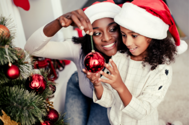 Mother and daughter holding a christmas tree ornament.