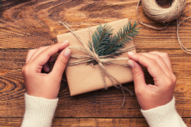 Close up of hands putting a twine bow on a wrapped present.