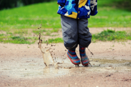 Child jumping in muddy puddle.