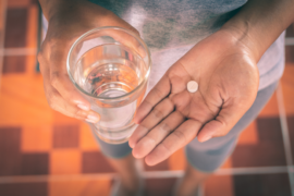 Female holding medicine pill and a glass a water.